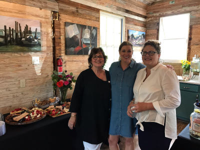 Three women smiling for a photo at the art show